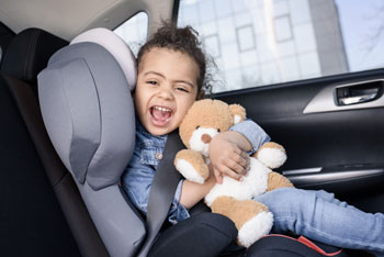 Little girl and teddy bear in the car seat