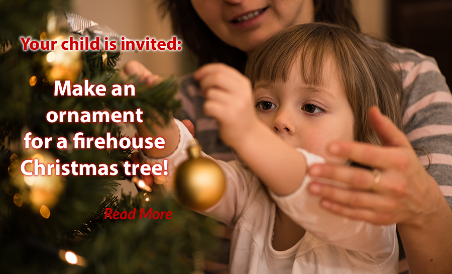 Child hanging a Christmas ornament on the tree